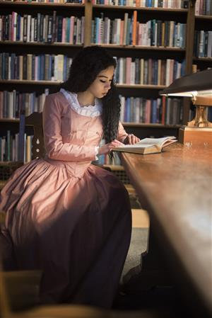 Photo of Emilee posing as Angelica from Hamilton, in a pink dress, sitting reading in a library