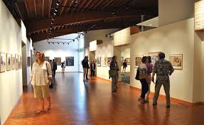 photo of a wide art gallery with people browsing